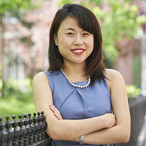 NYU Law graduate Alice Thai pictured in Washington Square Park with Vanderbilt Hall in the distance.